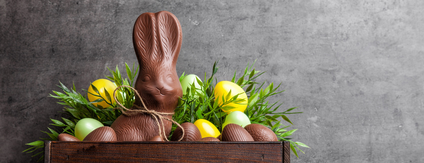 Traditional delicious Easter chocolate bunny and eggs inside a wooden crate