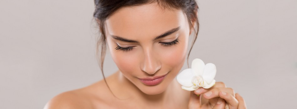 Beautiful young woman holding one orchid flower near face while looking down. Close up face of brunette woman with healthy skin and white flowers near face isolated on grey background. Beauty and body care concept.