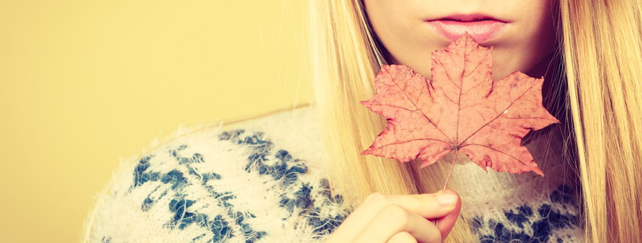 Autumnal natural decorations concept. Woman holding autumn leaf. Studio shot on orange background.