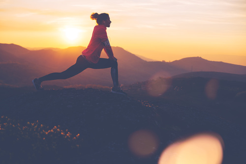 Silhouette of athletic girl doing stretching after a great jog i