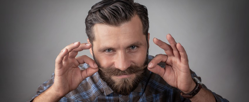 portrait of a man with a beard and mustache. man looking at camera to smiling. hands twirling a mustache. wearing a gray plaid shirt. gray eyes looking at the camera.
