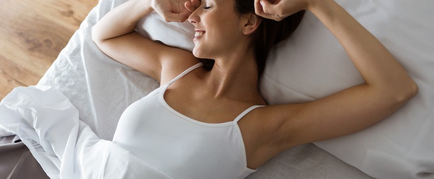 Portrait of beautiful young woman stretching in bed after wake up.