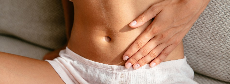 Young woman having Stomach Pain sitting on sofa at home close-up.