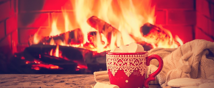 Mug of hot chocolate or coffee with marshmallows in a red mug on vintage wood table in front of Fireplace as a background. Christmas or winter warming drink.
